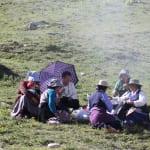 ガンデン寺の巡礼路でピクニックする家族連れ