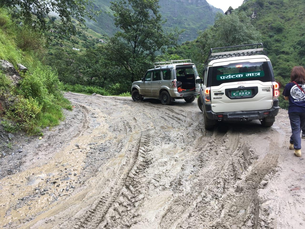 泥だらけの道を進むジープ
