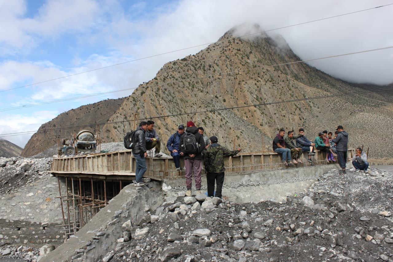 橋の建設現場にたむろする男たち