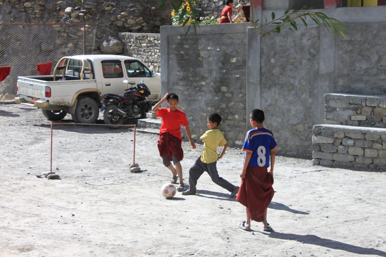 僧衣でサッカーに興じる小坊主