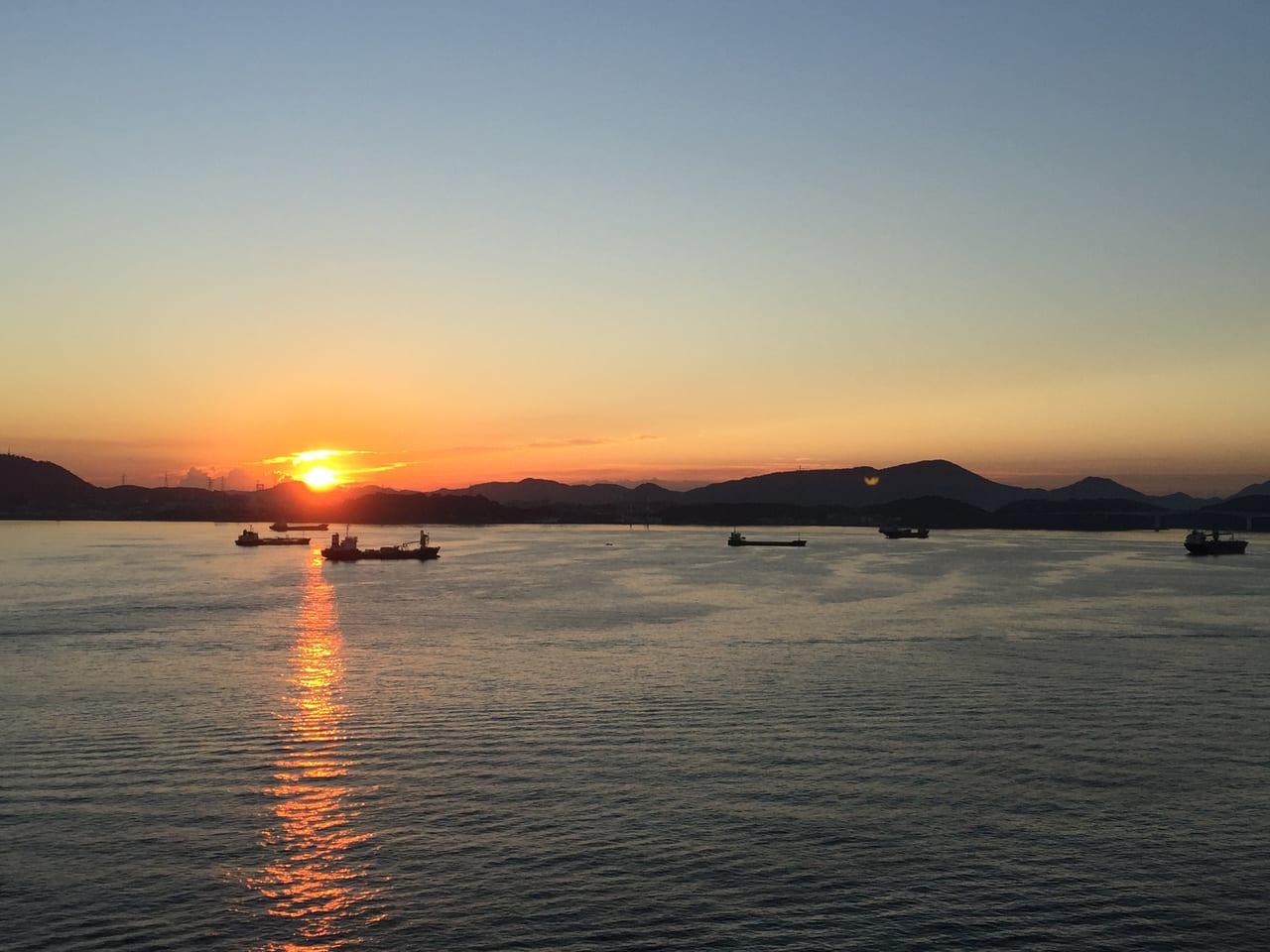関門海峡を航行する船上から日の出を臨む。