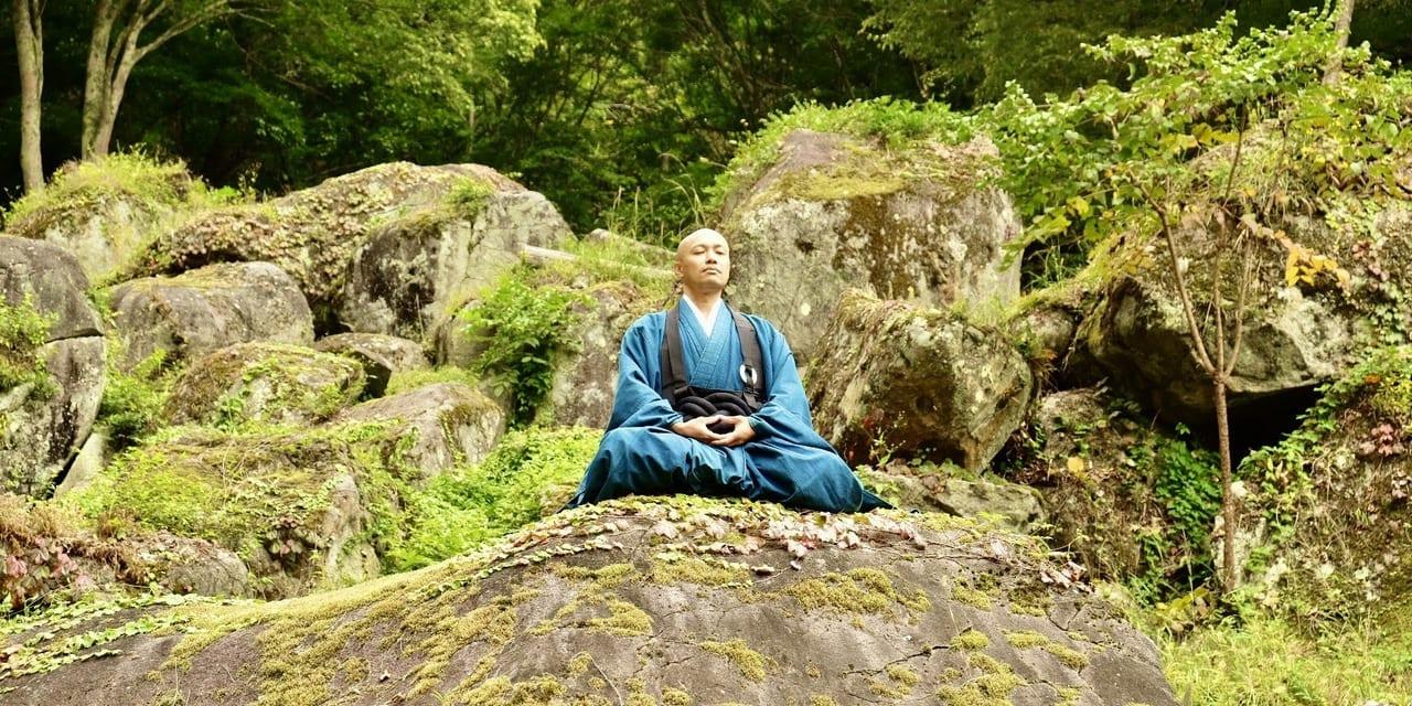 禅修行の場である石庭で座禅を組む青柳真元氏